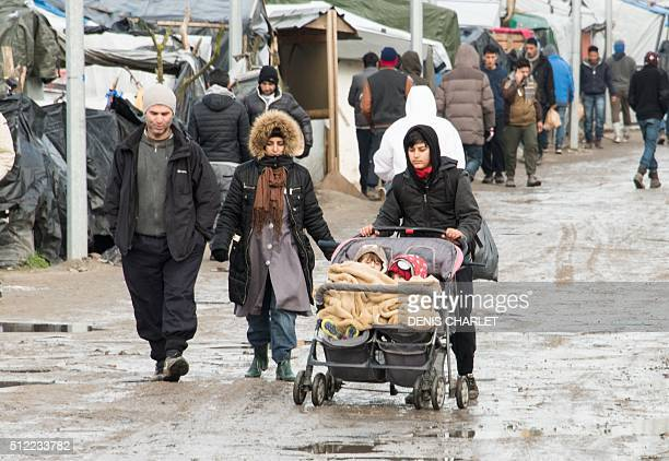 A woman pushes her children in a stroller on February 25 2016 in the Jungle migrants and refugee camp in Calais northern France A French court on...