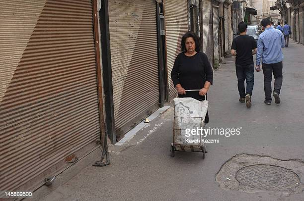A woman pushes her shopping cart in the back streets of Bab Tuma on May 29 2012 in Damascus Syria Despite all the ongoing conflicts in Syria people...