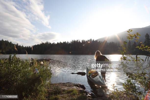 woman pushes kayak to lake edge, looks off to sunrise - canada stock pictures, royalty-free photos & images