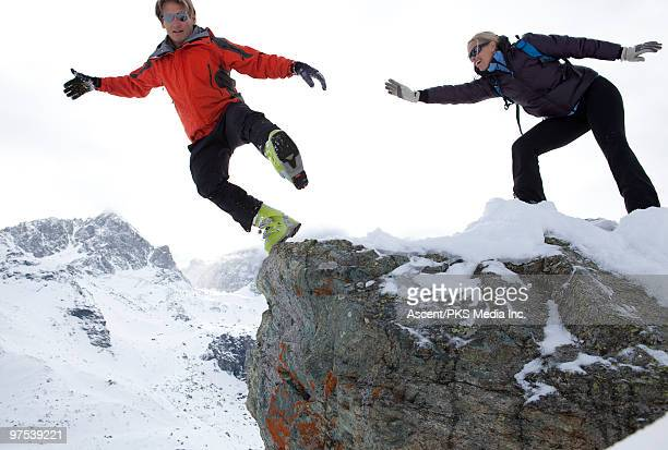 Woman pushes man off rock cliff above mountains