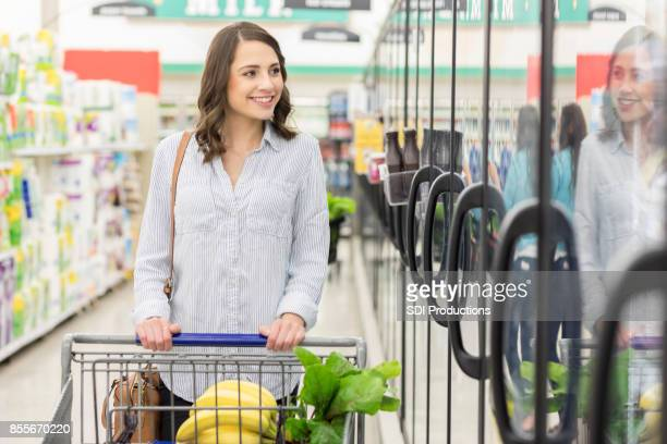 Woman pushes shopping cart in supermarket