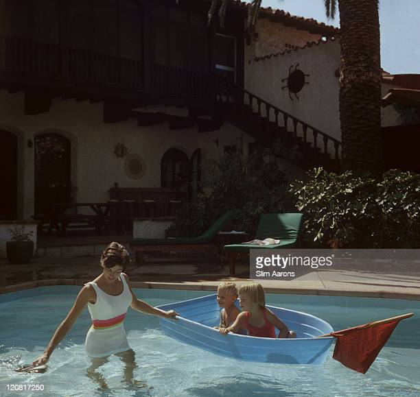 A woman pushing a boy and a girl in their toy boat in a swimming pool at a house in Laguna Beach California October 1956