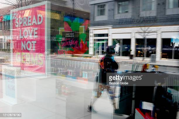 A woman pushing a cleaning cart walks past a store with a sign reading Spread Love Not Germs as retail shops remain closed in Assembly Square in...