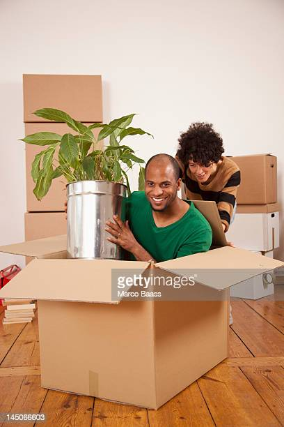 A woman pushing a man sitting inside of a moving box