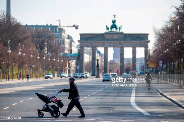 Woman pushing a pram crosses an almost deserted 17th June street near Brandenburger gate in Berlin on April 1, 2020 as Germany continues its battle...