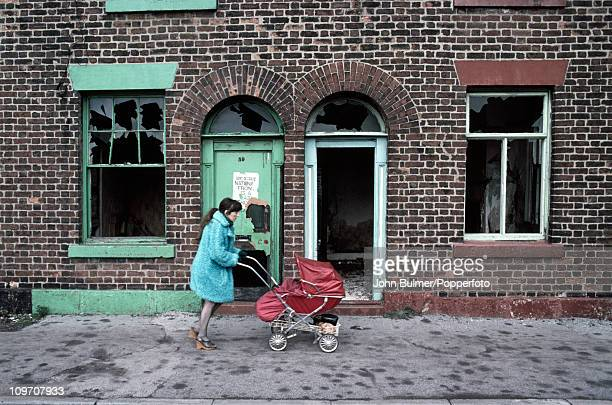 A woman pushing a pram past derelict houses Manchester England in 1976 On the door behind her is an antiNational Front poster reading 'Don't be...