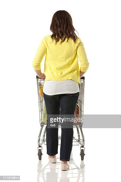 Woman pushing a shopping cart in supermarket