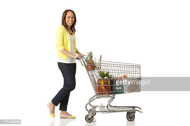woman pushing a shopping cart - shopping cart stock pictures, royalty-free photos & images