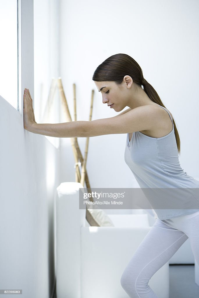 Woman pushing against wall, side view : Stock Photo