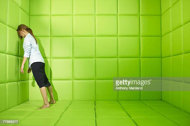 Woman pushing against walls of green padded cell