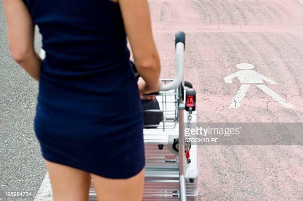 Woman pushing baggage cart on crosswalk