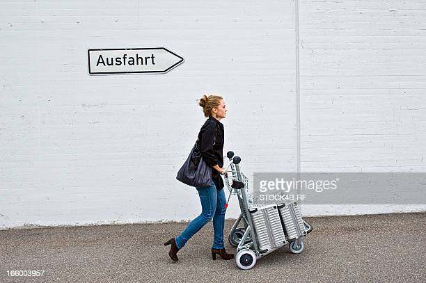 Woman pushing baggage cart under German exit sign