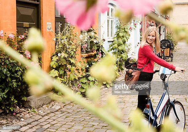 Woman pushing bicycle on cobblestone street, Aarhus, Denmark