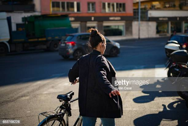 woman pushing bike through the city - one young woman only stock pictures, royalty-free photos & images
