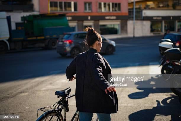woman pushing bike through the city - endast en ung kvinna bildbanksfoton och bilder