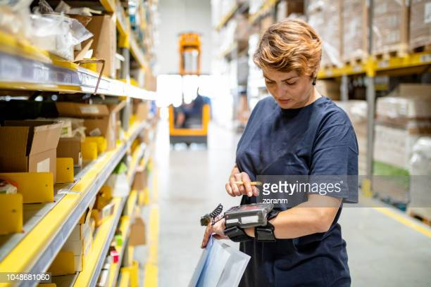 woman pushing buttons on wearable barcode reader - automation stock pictures, royalty-free photos & images