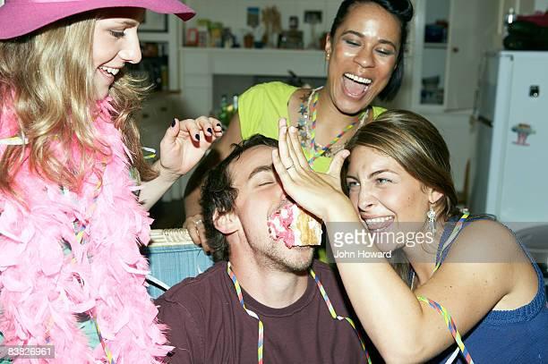 Woman pushing cake into man's mouth