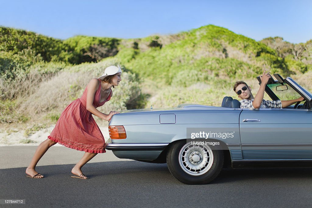 Woman pushing car as boyfriend steers : Stock Photo
