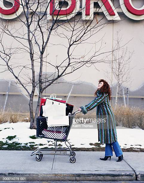 woman pushing cart filled with shopping bags outside mall - voll stock-fotos und bilder