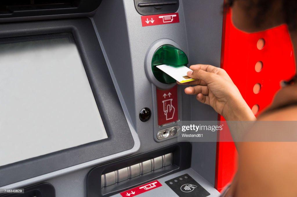 Woman pushing credit card at cash dispenser, partial view : Stock Photo