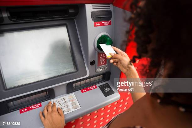 Woman pushing credit card at cash dispenser