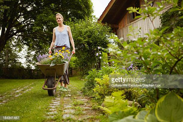 Woman pushing flowers in wheelbarrow
