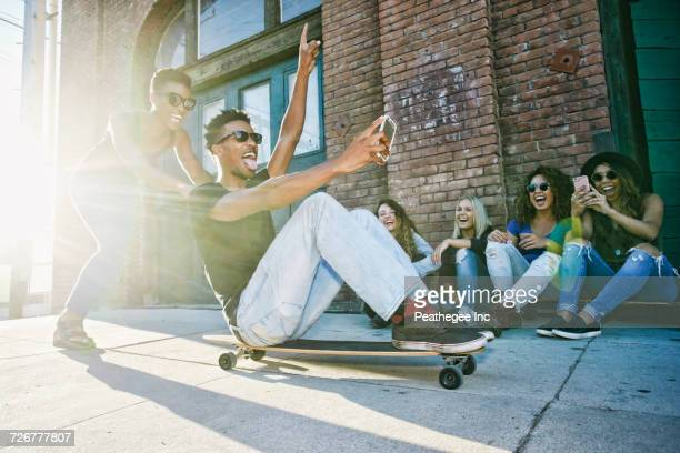 woman pushing friend sitting on skateboard in city - skating stock photos and pictures