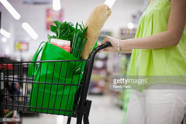 woman pushing grocery car - reusable bag stock pictures, royalty-free photos & images