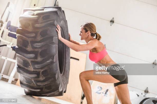 Woman pushing heavy tire in gymnasium
