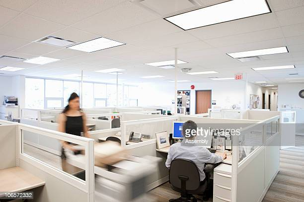 woman pushing mail cart in office