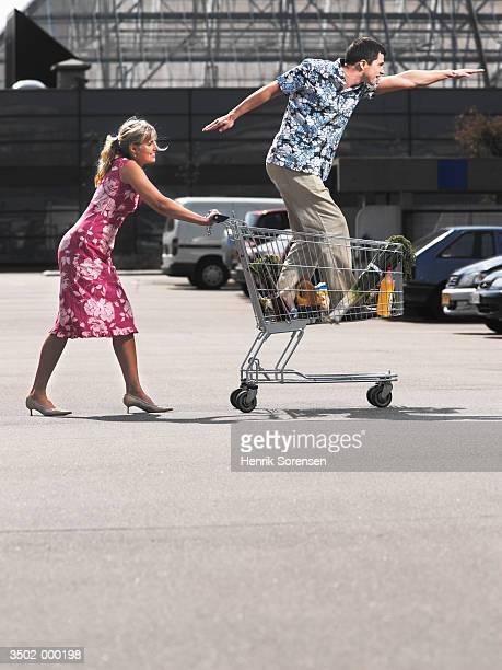 Woman Pushing Man in Cart