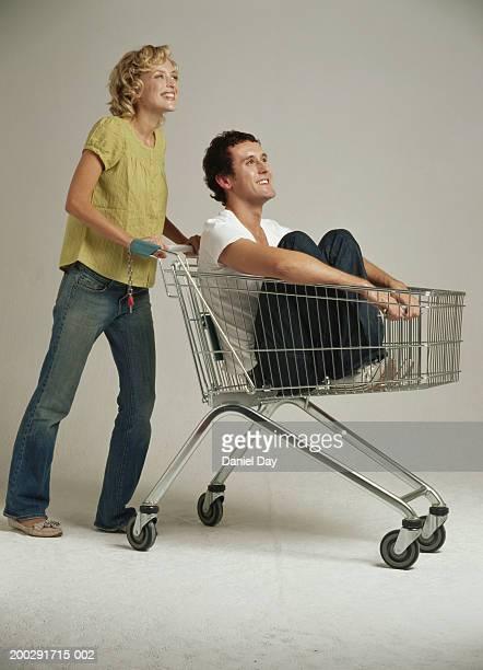 Woman pushing man sitting in shopping trolley, smiling