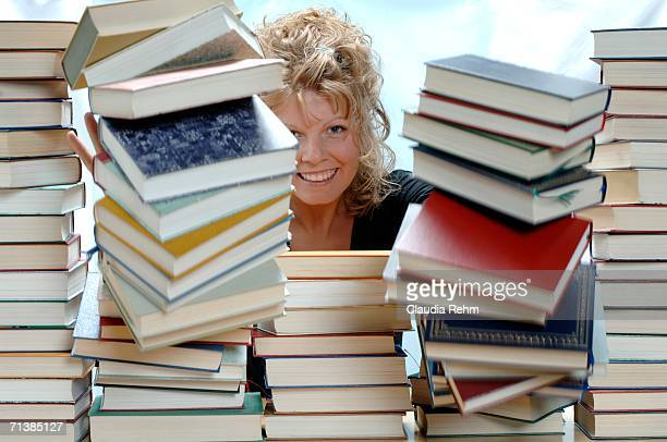 Woman pushing pile of books, smiling, portrait