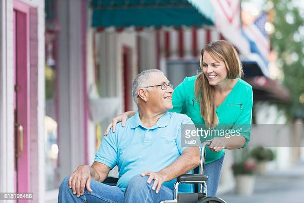 Woman pushing senior man in wheelchair, outside stores.