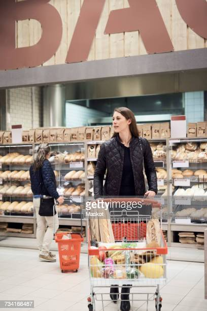 Woman pushing shopping cart against female standing by bread rack at supermarket
