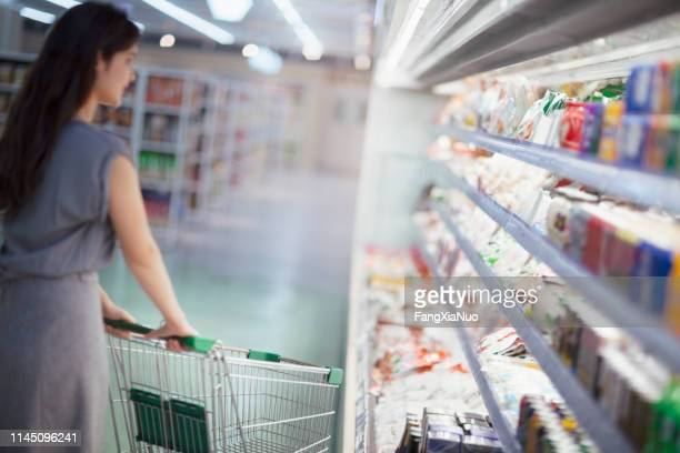 mulher que empurra o carro de compra no supermercado - mercado espaço de venda no varejo - fotografias e filmes do acervo