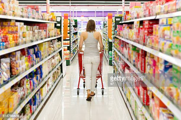 woman pushing shopping cart looking at goods in supermarket - full stock pictures, royalty-free photos & images