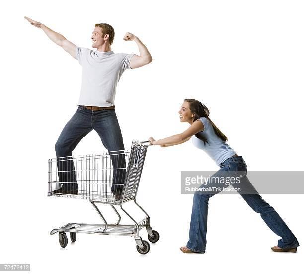 Woman pushing shopping cart with boyfriend inside