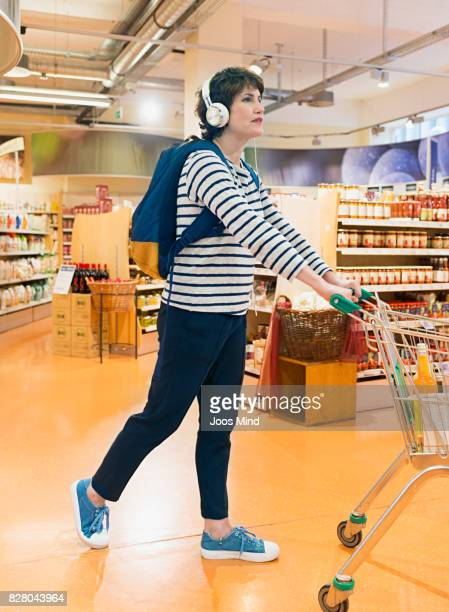 woman pushing shopping trolley , wearing headphones
