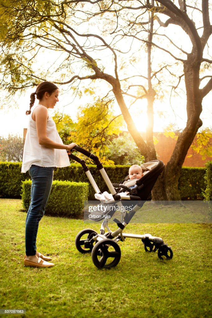 Woman pushing stroller with baby : Stock Photo