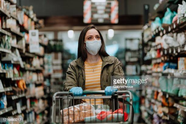 woman pushing supermarket cart during covid-19 - merchandise stock pictures, royalty-free photos & images
