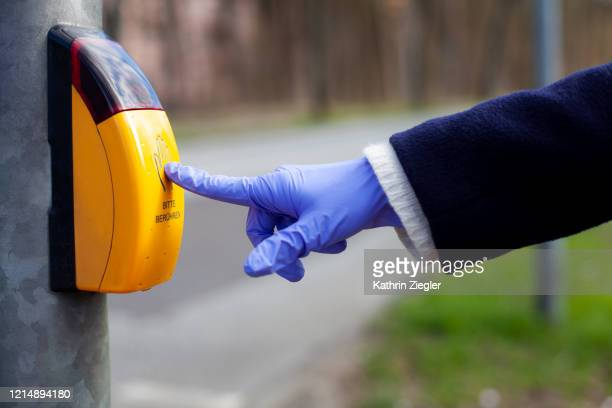 woman pushing the button at crossroads sign, wearing protective gloves - walk don't walk signal stock pictures, royalty-free photos & images