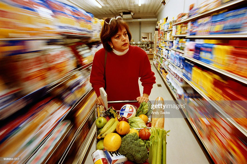 Woman pushing trolley in supermarket aisle (blurred motion) : Stock Photo