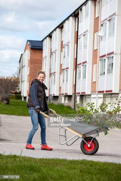 Woman pushing wheelbarrow