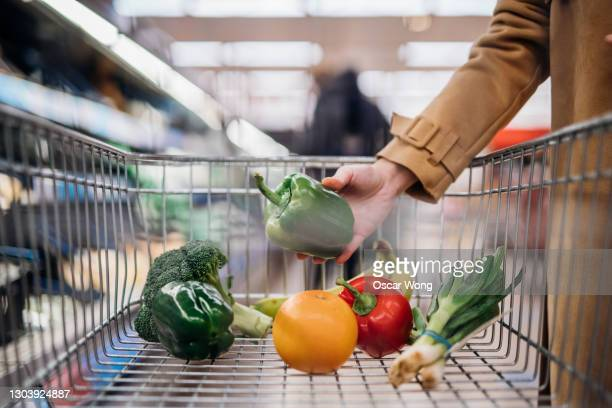 woman put down green pepper in shopping trolley at supermarket - supermarket stock pictures, royalty-free photos & images
