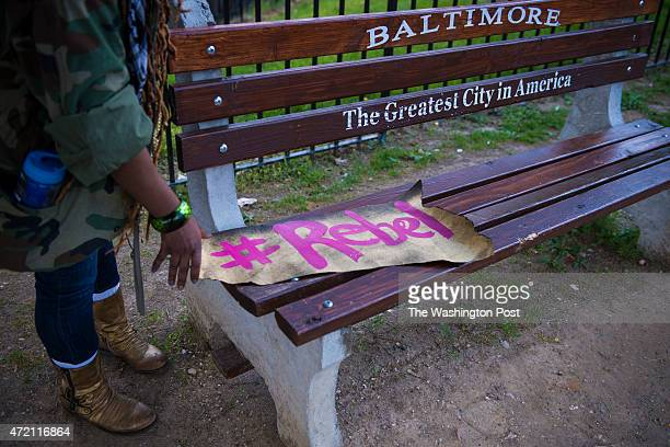 A woman put down her protest sign on a bench as protestors march around the city in solidarity with Freddie Gray after it was announced that criminal...