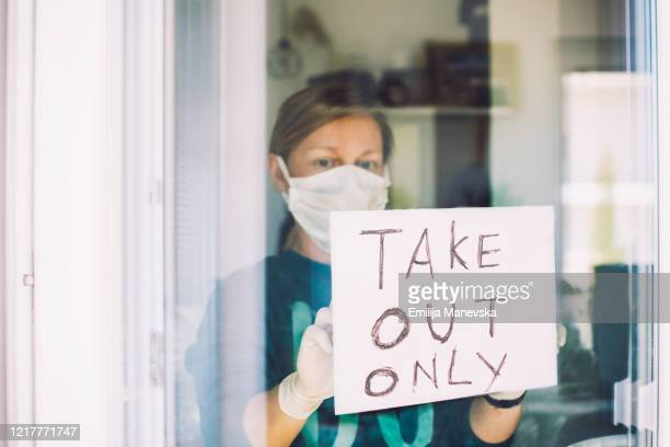 "woman put ""take out only"" sign on front door shop - essential workers stock pictures, royalty-free photos & images"