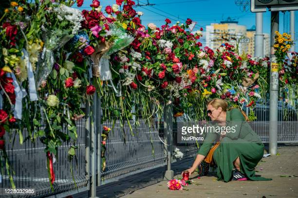 Woman puts a candle in a flowered memorial where a man was killed in clashes between police riot and people during a protest in Minsk against the...