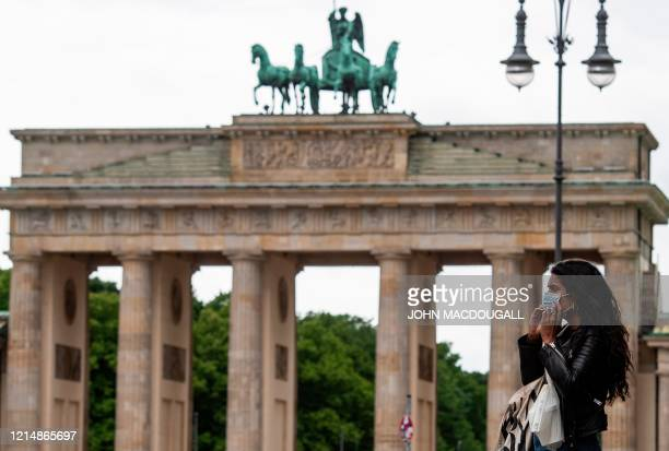 Woman puts a face mask on before entering a coffee shop in front of the Brandenburg Gate in Berlin on May 24, 2020 during the new coronavirus...