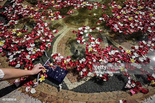 A woman puts a flower into the pond at the Bali Bombing Memorial Monument on October 12 2014 in Kuta Bali Indonesia Today marks the 12th anniversary...